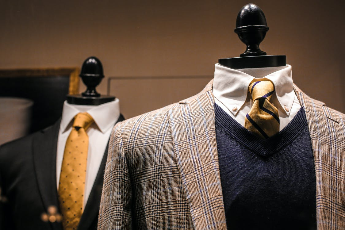Dandy fancy jackets with shiny ties on dummies in showroom of contemporary male shop