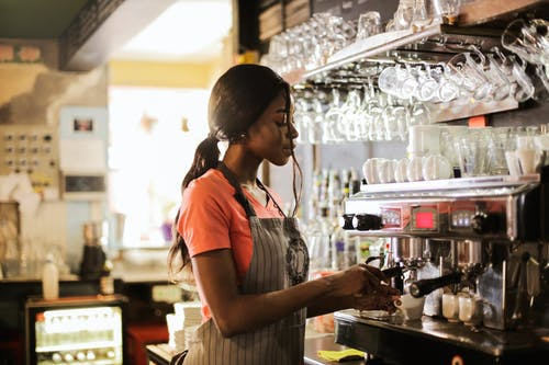 Woman Preparing Coffee latte Near Espresso Machine