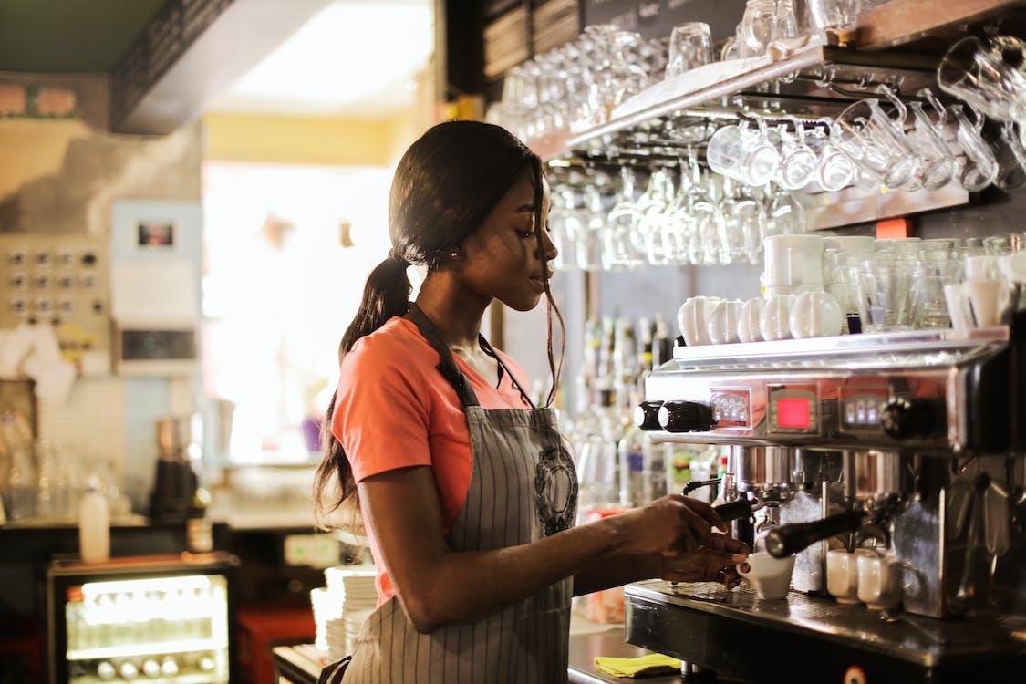Woman Preparing Coffee latte Near Espresso Machine
