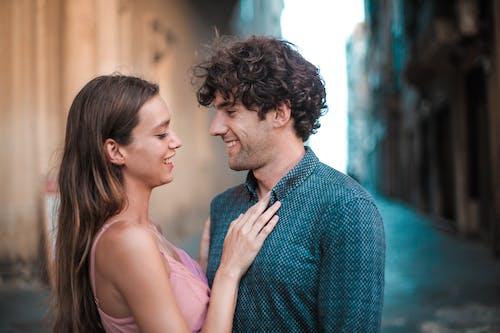 Man Wearing Blue Shirt Kissing Woman in Pink Tank Top