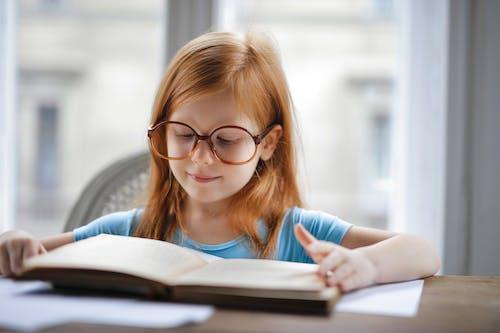 Girl in Blue Shirt Wearing Eyeglasses Reading Book