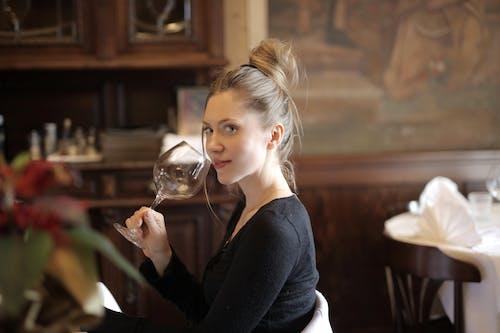 Donna Dei Capelli Biondi In Maniche Lunghe Nere Che Tengono Il Bicchiere Di Vino