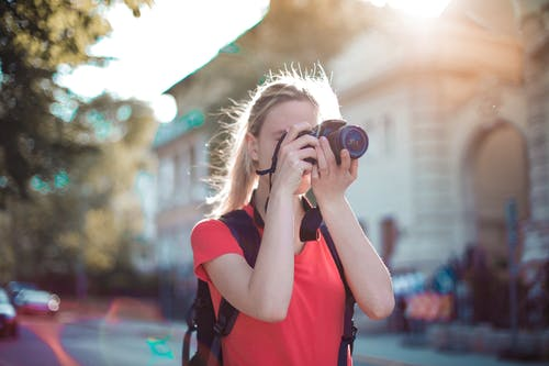 Woman in Red Shirt Taking Pictures Using Dslr camera
