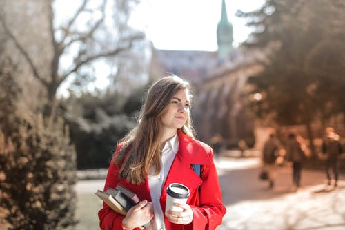 Woman in Red Coat Holding Notebooks and Coffee cup
