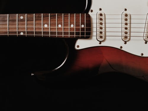close-Up Photo of White Electric Guitar