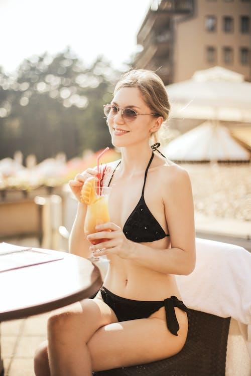 Woman in Black Bikini Top Holding Cocktail Glass