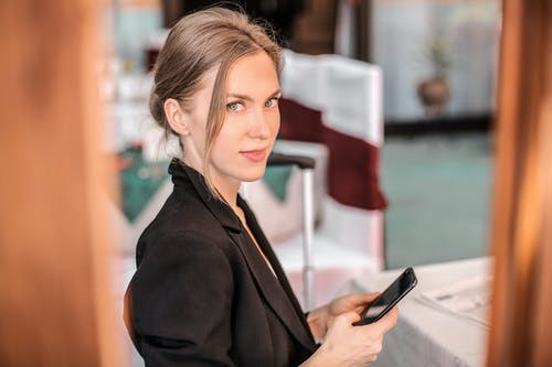 Woman in Black Coat Holding Black Smartphone