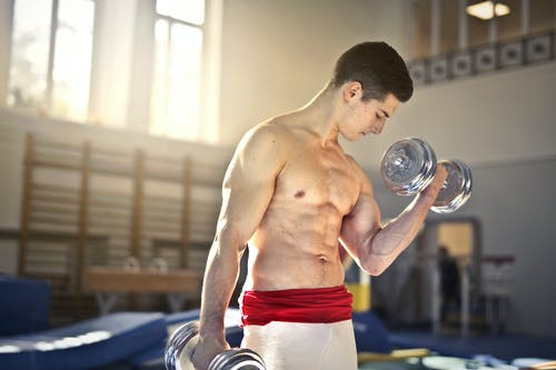 Topless Man Lifting a Silver Dumbbells