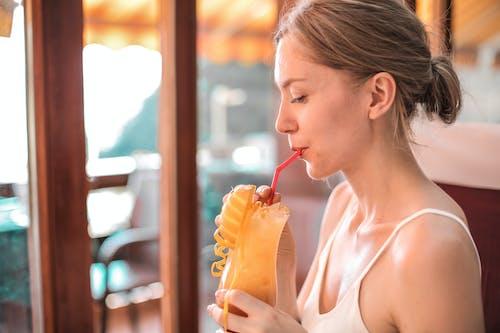Woman in White Tank Top Drinking Orange Juice