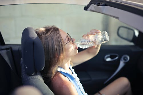 High angle side view of young woman in glasses and casual clothes drinking water from plastic transparent bottle while sitting in cabriolet with open roof in traffic jam in hot sunny day
