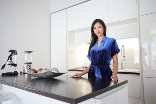 Woman in Blue Dress Standing Beside Counter