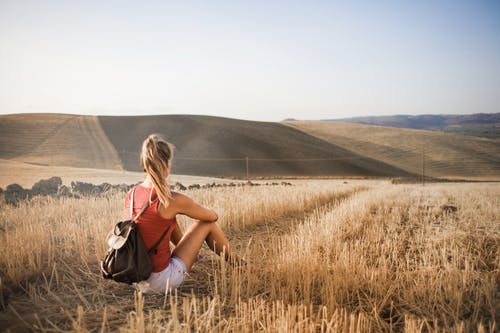 Woman in Red Tank Top and White Shorts Carrying Backpack Sitting on Brown Grass Field