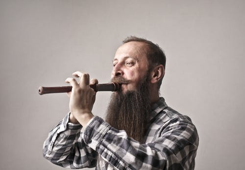 Man in Black and White Plaid Dress Shirt Playing Flute