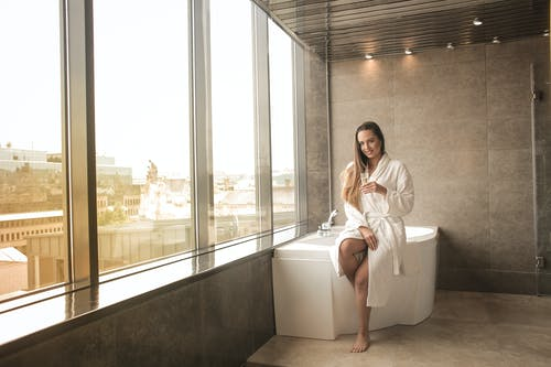 Woman in WHITE Bathrobe Sitting on White Bathtub