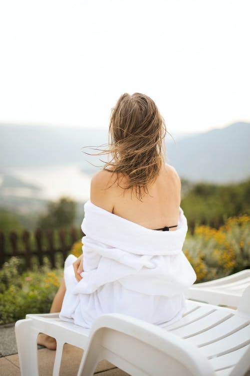 Back View Photo of Woman in White Robe Sitting on White Pool Chair