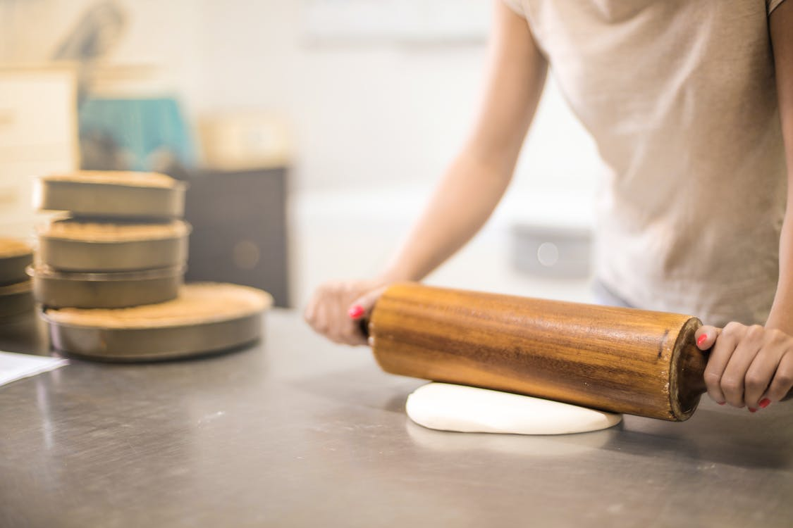 Person in White T-shirt Rolling a Pin in Dough
