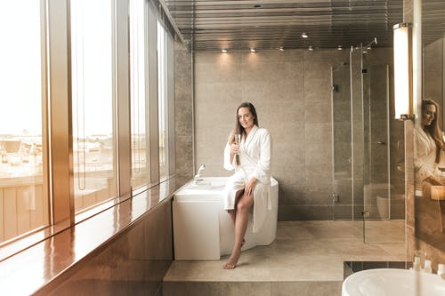 Photo of Smiling Woman in White Bathrobe Sitting on White Bathtub While Holding a Glass of Champagne