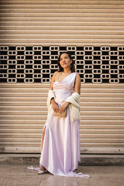 Photo of Woman in Stylish Sleeveless Dress Standing In Front of Roll Up Door