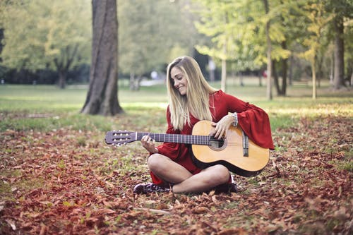 Woman in Red Long Sleeve Dress Playing Brown Acoustic Guitar Sitting on the Ground