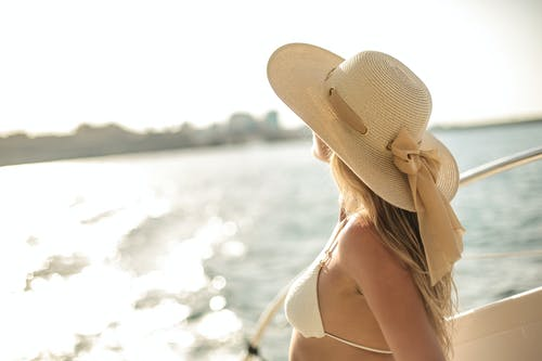 Back view of slim female in bikini top and straw hat enjoying trip on cruise boat on sunny day while relaxing during summer vacation and looking away