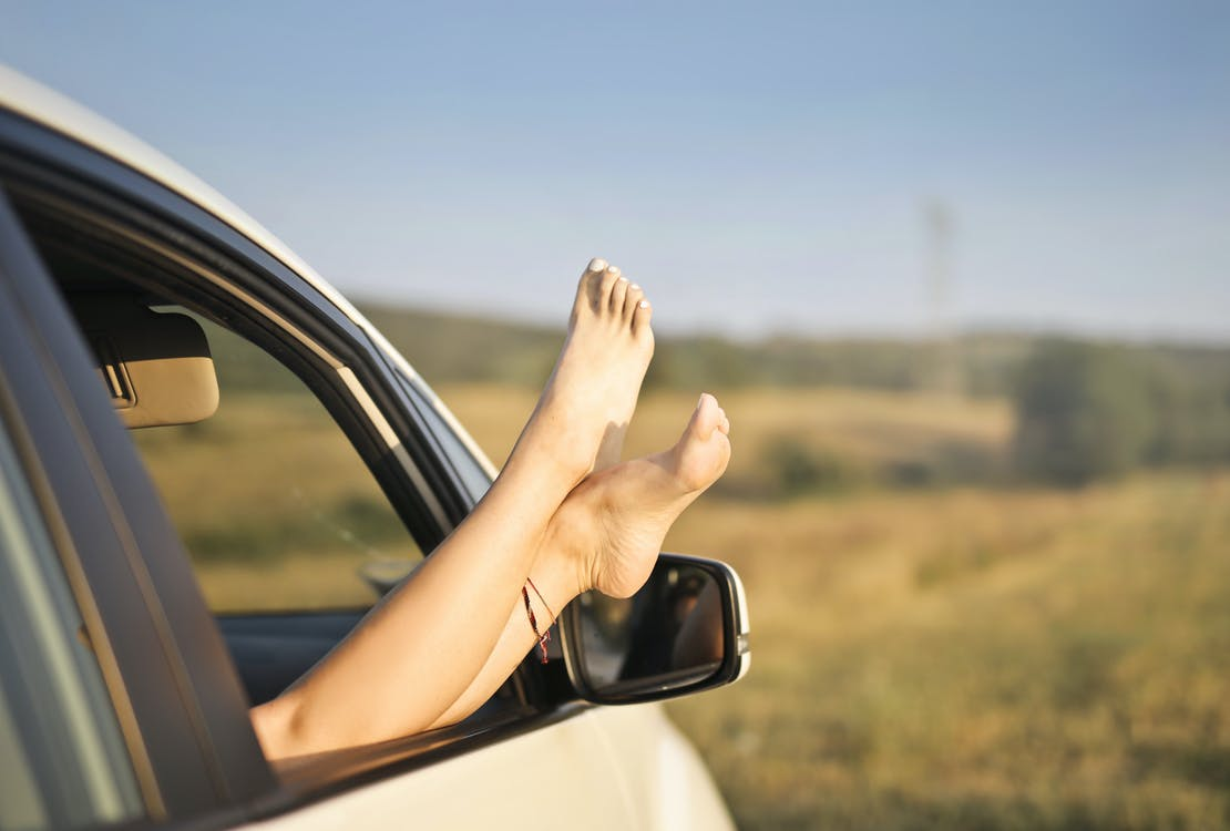 Crop carefree woman with legs sticking out of car window