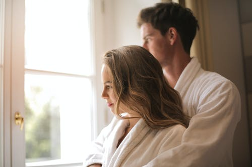 Gentle couple hugging near window at home