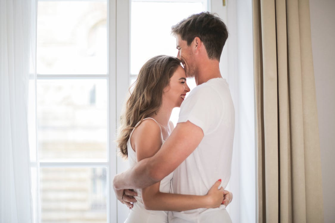 Man in White T-shirt Embracing Woman in White Tank Top