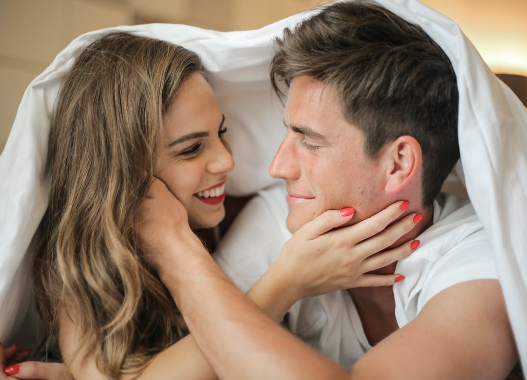 Gentle couple touching each other under duvet