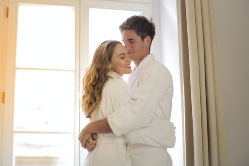 Man in White Bathrobe Embracing Woman in White Bathrobe