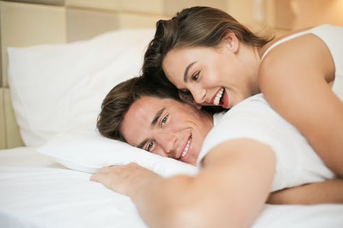 Cheerful couple hugging on bed in comfortable bedroom