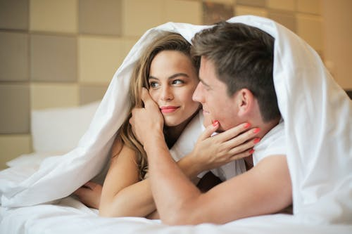 Cheerful couple lying under blanket on bed