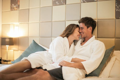 Delighted couple lying on bed in cozy bedroom and cuddling