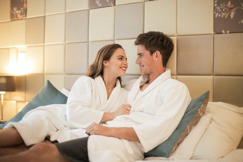 Couple in love relaxing on bed in bathrobes during weekend