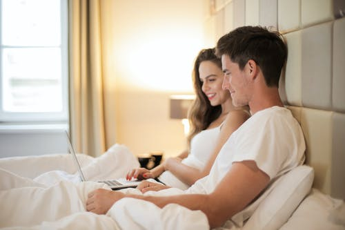 Happy couple using laptop on bed during weekend