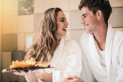 Side view of content couple in bathrobes relaxing on bed with platter of mixed fruit and looking at each other