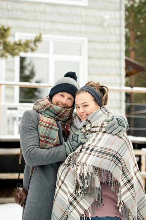 Man In Gray Coat Hugging Girl Wearing Plaid Scarf