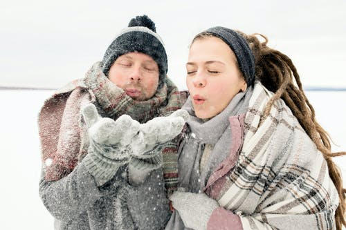 People Blowing Snow From Man's Hands