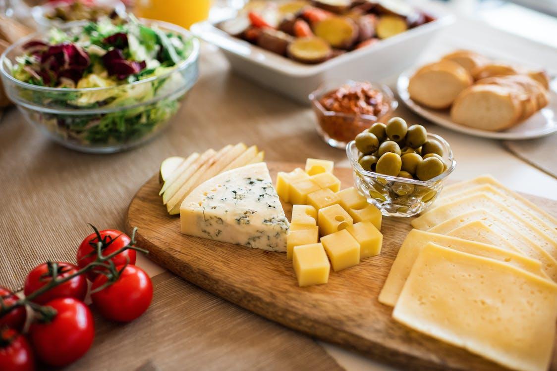 茶色の木製まな板にチーズと赤いトマト