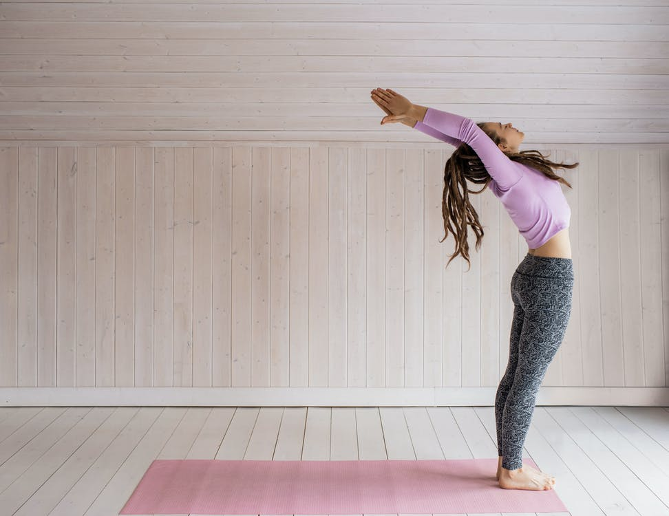 Woman In Pink Long Sleeves Top And Gray Leggings Doing Yoga