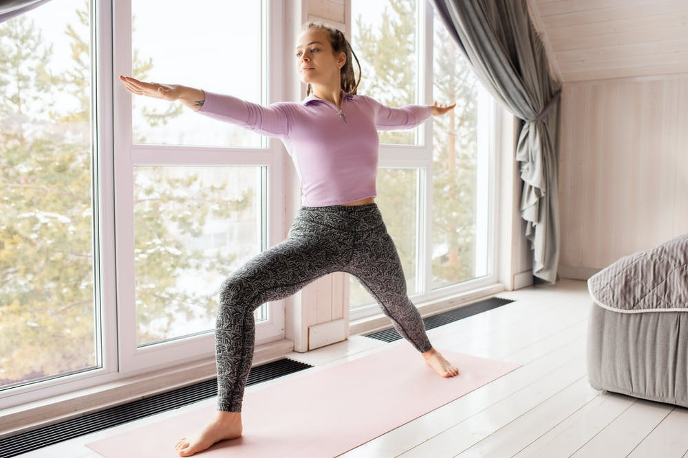 A woman in a strong yoga position. Next to big windows in a brightly lit house.
