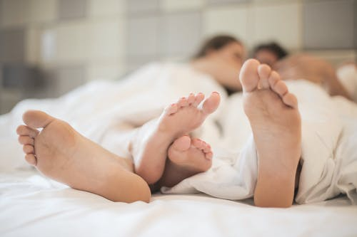 Feet of couple in love in bed