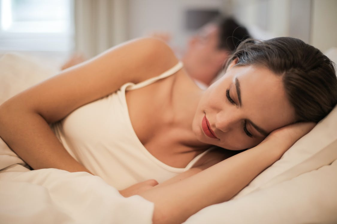 Charming woman sleeping in bed at home