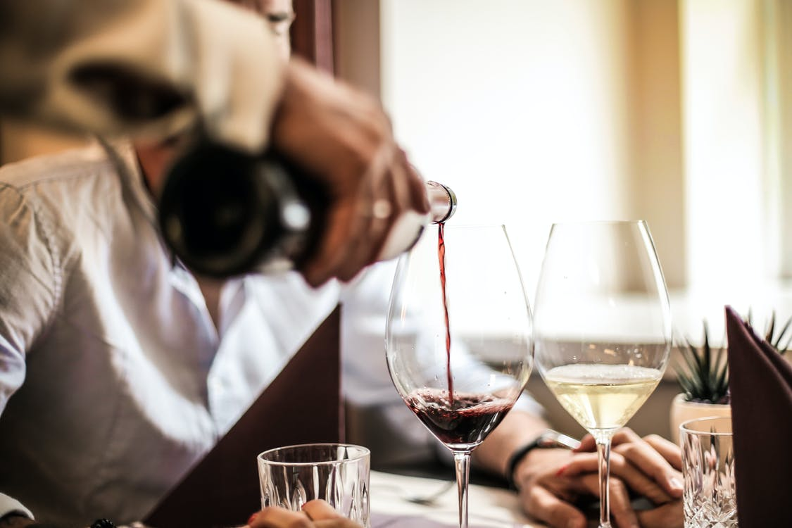 Crop man pouring red wine in glass in restaurant