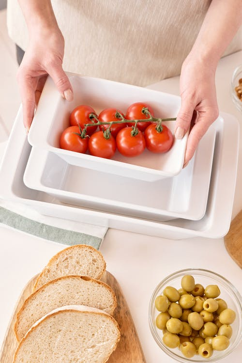 Person Holding White Ceramic Tray With Red Tomatoes
