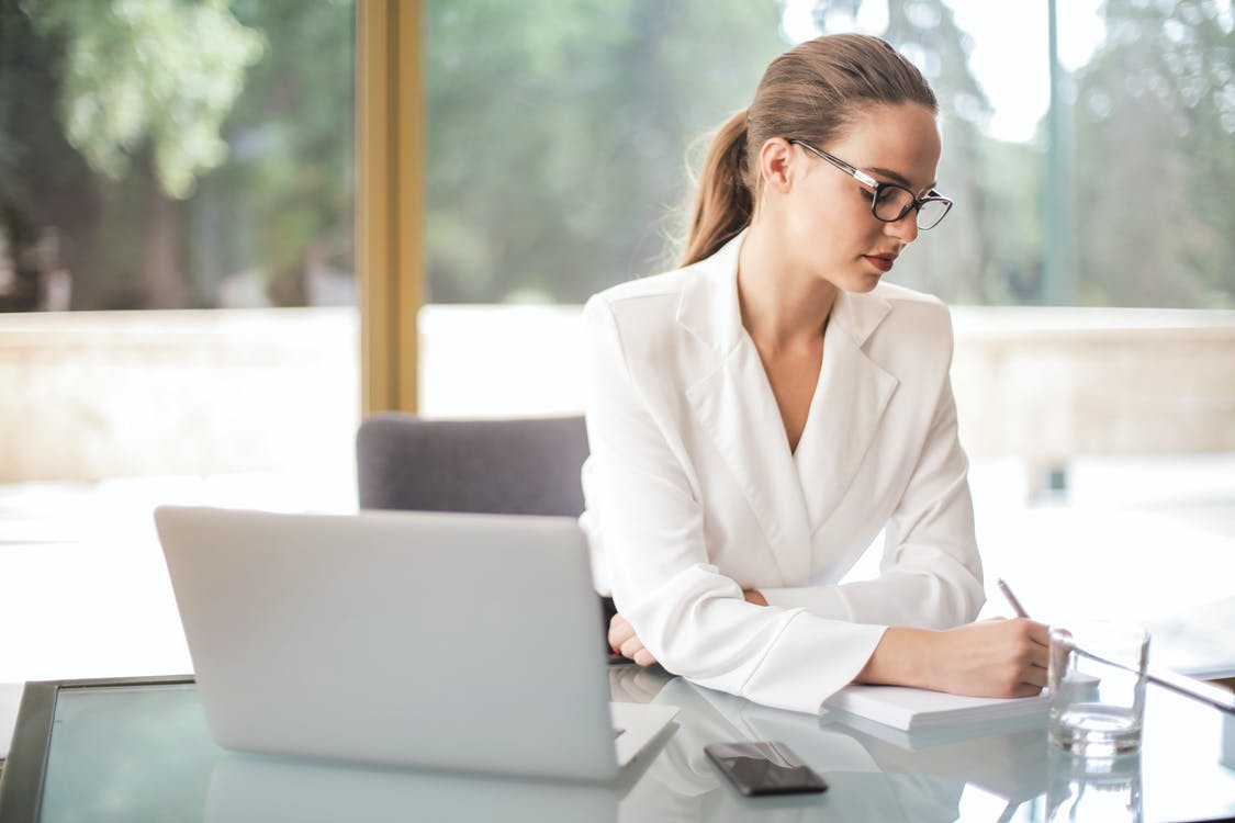 Thoughtful businesswoman taking notes in notebook in bright office