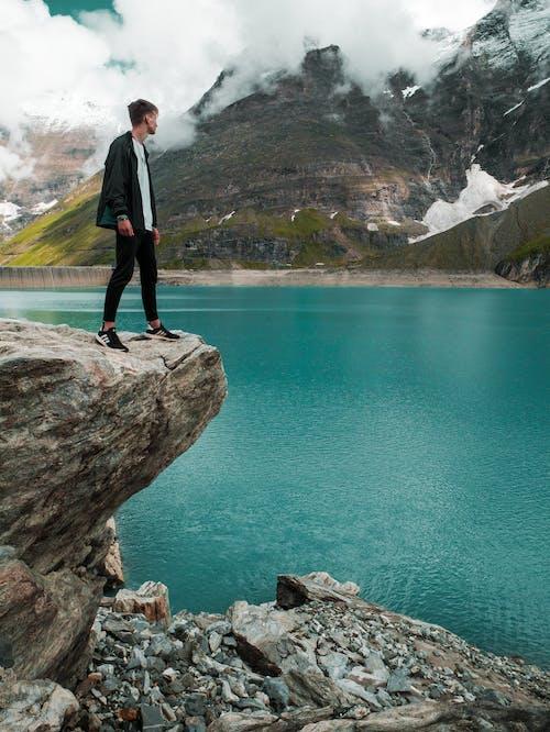 Man in Black Pants Standing on Rock Near Body of Water