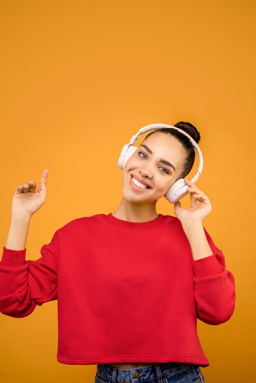 Woman in Red Sweater Wearing White Headphones