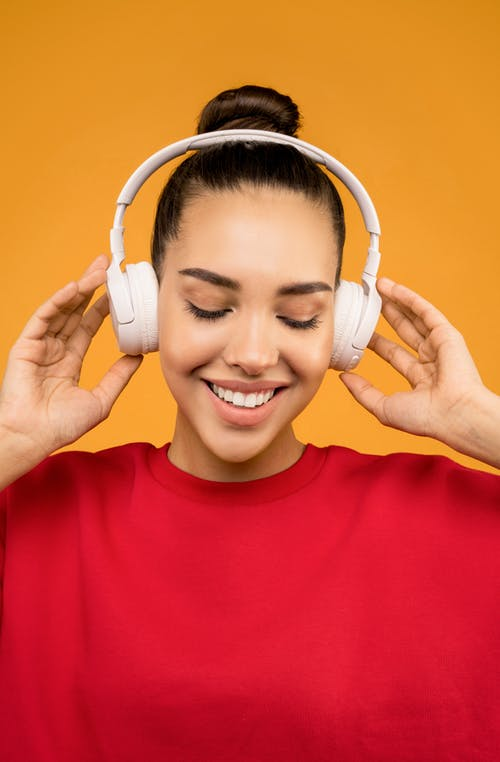 Happy Woman Listening Music on White Headphone
