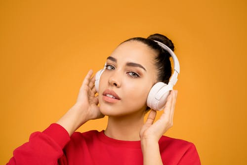 Woman Red long Sleeves Holding White Headphones