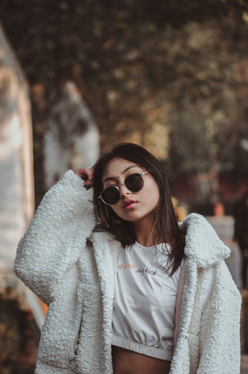 Woman in White Crop Top Shirt Wearing Black Shades